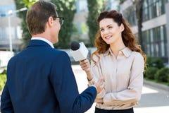 periodista de sexo femenino sonriente que toma entrevista fotografía de archivo