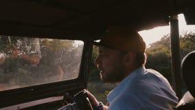 Periodista de sexo masculino enfocado feliz joven con la cámara profesional en paseo de la puesta del sol en viaje del coche de l almacen de video