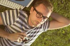 Periodista que miente en la hierba Imagenes de archivo
