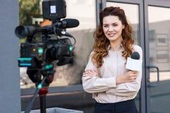 periodista sonriente con el micrófono que se coloca delante de digital imagen de archivo libre de regalías