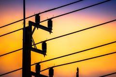Periodo crepuscolare, siluette della posta della lampada e linea telefonica con un tramonto del fondo sulla via thailand immagini stock