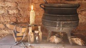 Periodo della notte della strega con le candele ed il vaso con fuoco fra le ragnatele e la terra antica stock footage