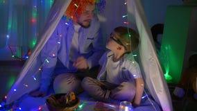 Periodo di svago, il bambino piacevole dice i segreti del padre allegro nella parrucca che si siede nel tepee nella sera stock footage