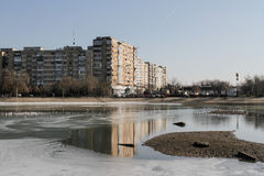 Periphery landscape. Bucharest, Romania, 7 February 2016: Landscape with tall residential blocks and lake in a Bucharest suburb stock image