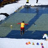 People enjoy Pond Skimming, a fun way to celebrate the end of the winter season. Perisher, Australia - Sept 30, 2018. People enjoy Pond Skimming. The pond-skim royalty free stock photo