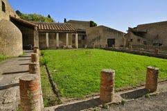 Peristylium, Herculaneum. Peristyle with Grass in Ancient Herculaneum. Herculaneum was buried in the eruption of Mount Vesuvius in AD 79. Unlike Pompeii, the Stock Image