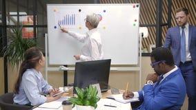 Perito financeiro fêmea que apresenta a estratégia empresarial à equipe da raça misturada na instrução vídeos de arquivo