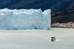 Boat cruising along lake in front of Perito Moreno Glacier stock photo