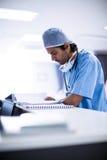 Perizie mediche della lettura del chirurgo Fotografia Stock