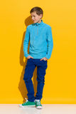 Perky boy. Young boy posing with hands in pockets. Full length length studio shot on yellow background Stock Photos