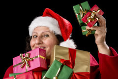 Perky Female Pensioner Presenting Wrapped Gifts. Cheerful aged woman with Santa Claus cap is offering three small Christmas gifts in her raised left hand. More Stock Images