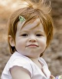 Perky Little Girl. A little redheaded girl with messed up hair and a smirk instead of a smile Stock Image