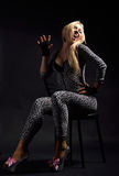 Perky woman in the catsuit dappled. Fervent woman is imitating a cat. She is sitting on the chair in the dark. She is wearing a spotty slinky catsuit and high Royalty Free Stock Images