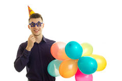 Perky young guy keeps near eye paper glasses and lots of colored balls. Is  on a white background Stock Photography