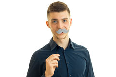 Perky young guy with paper mustache. Isolated on white background Stock Photo