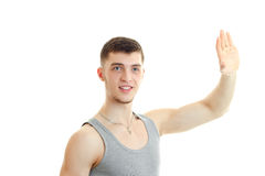 Perky young guy waving his hand and looks away. Isolated on white backgroud Stock Photo