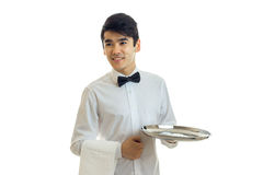 Perky young waiter looks to the side and holding a blank tray for eating Royalty Free Stock Images