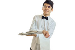 Perky young waiter in a white shirt with black bow tie holding a towel and tray for dishware. On white background Royalty Free Stock Images