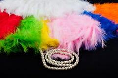 Perl项链在软的五颜六色的羽毛附近放置在黑织品背景 免版税库存照片