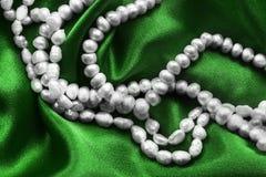 Perla en el satén verde Fotografía de archivo libre de regalías