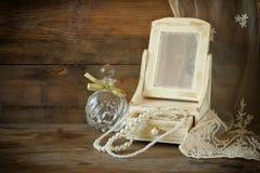 Perlas del vintage, joyero de madera antiguo con el espejo y botella de perfume en la tabla de madera Imagen filtrada Foto de archivo libre de regalías