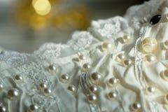 Perlas minúsculas bordadas sobre un vestido de boda Imagenes de archivo