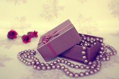 Perlas rosadas en un rectángulo de joyería imagenes de archivo