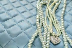 Perlas y colgante en fondo azul Fotografía de archivo