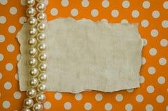Perlas y fondo punteado naranja Fotos de archivo