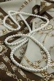 Perle bianche su una sciarpa del progettista Fotografie Stock