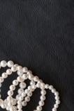 Perle bianche sulla seta nera come fondo Fotografie Stock Libere da Diritti