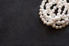 Perle bianche sulla seta nera come fondo Fotografia Stock