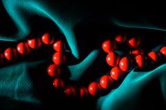Perle del corallo rosso in ombre drammatiche dure Immagine Stock