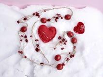 Perle di legno rosse, cuori fatti a mano sulla neve, vista superiore, concetto del feltro delle congratulazioni sul San Valentino immagine stock libera da diritti