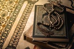 Perle di preghiera sul libro sacro del Corano dei musulmani fotografia stock libera da diritti