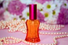 Perle di vetro rosse della bottiglia e della perla di profumo immagine stock libera da diritti