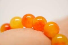 Perle giallo arancione del braccialetto sul polso fotografie stock libere da diritti