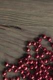 Perle metalliche rosse luminose su superficie di legno rustica fotografie stock