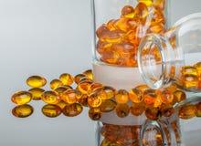 Perle molli ovali vitamina A, E, olio di pesce, olio dell'enagra su fondo grigio Fotografie Stock Libere da Diritti