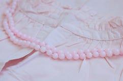 Perle rosa sopra il vestito d'annata dal cotone della donna Immagine Stock