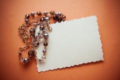 Perle scure su fondo arancio Fotografie Stock Libere da Diritti
