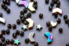 Perle variopinte e nere e pietre isolate su fondo grigio fotografie stock