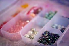 Perle variopinte in primo piano di due contenitori Fotografia Stock