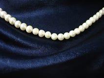Perlen auf Hintergrund die dunkelblaue Seide lizenzfreie stockfotografie