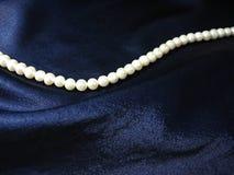 Perlen auf Hintergrund die dunkelblaue Seide stockfotos