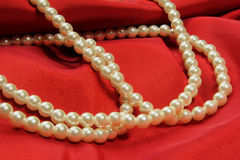 Perlen auf rotem Gewebe Stockfoto