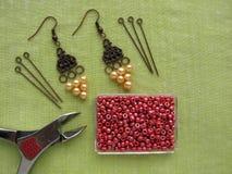 Perlen, Möbel und Werkzeuge für die Herstellung von Ohrringen, handgemachter Schmuck Stockfotos