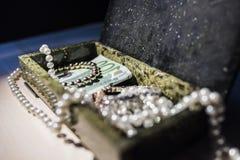 Perlen Sie, Goldarmband und Geld in einem Kasten Stockfotos