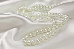 Perlen Sie Halskette auf einem Satin- oder Seidenhintergrund Stockfoto