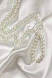 Perlen Sie Halskette auf einem Satin- oder Seidenhintergrund lizenzfreie stockbilder
